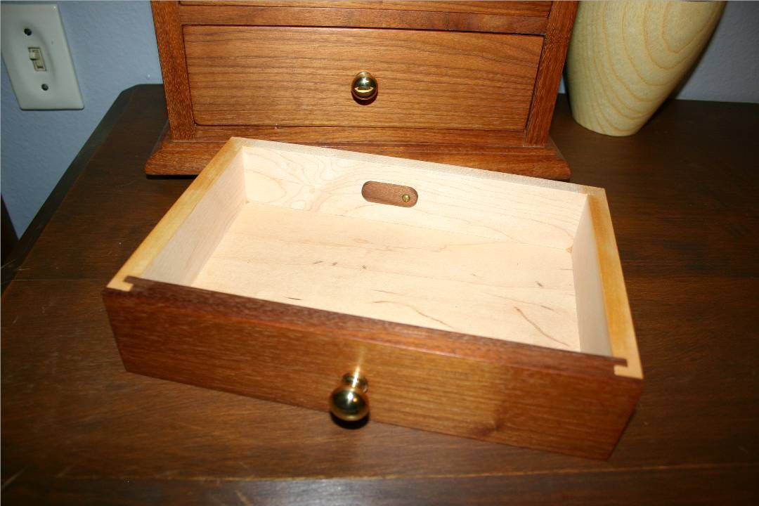 Small walnut tab at back of each drawer.